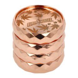 Drtič tabáku kovový Super Heroes Copper, 53mm-Kvalitní kovový drtič tabáku Super Heroes Copper. Masivní čtyřdílná drtička v měděném lesklém provedení se závitem, sítkem a zásobníkem na tabák. Logem a listy konopí zdobené víčko drtičky je magneticky uzavíratelné. Ostré hroty ve tvaru diamantu nadrtí velmi jemně vaší směs. Drtič je dodávaný v kartonové krabičce. Rozměry: průměr 53mm, výška 50mm.