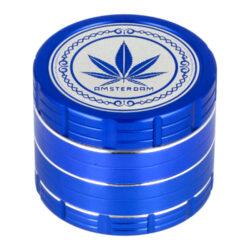 Drtič tabáku kovový Amsterdam Blue, 4.díl., 50mm-Kovový drtič tabáku Amsterdam Blue. Atraktivní čtyřdílná drtička se závitem, sítkem a zásobníkem na tabák je vyrobena z kvalitního hliníku CNC technologií. Kvalitně zpracovaný povrch s jemným drážkováním v modrém metalickém provedení je upraven eloxováním. Horní strana víčka je zdobená logem Amsterdam. Jednotlivé díly drtičky na tabák jsou pevně spojené na závit, víčko je na magnet. Precizně broušené ostří nožů velmi jemně nadrtí vaši směs do požadované hrubosti. Drtič tabáku Amsterdam je dodávaný v kartonové krabičce.  Průměr drtiče: 50 mm Výška drtiče: 40 mm